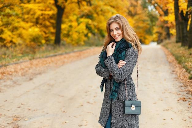 Gelukkig mooie jonge vrouw in een herfst jas met een sjaal op een achtergrond van geel gebladerte