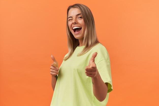 Gelukkig mooie jonge vrouw in gele t-shirt knipogen en wijzend op je aan de voorkant door vingers naar beide handen geïsoleerd over oranje muur