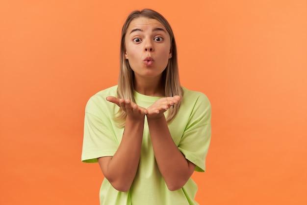 Gelukkig mooie jonge vrouw in gele t-shirt met lege ruimte op de handpalmen en het verzenden van een kus geïsoleerd over oranje muur kijkend naar de voorkant