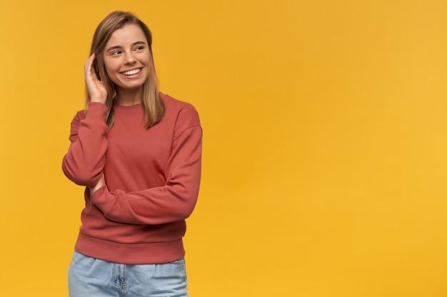 Gelukkig mooie jonge vrouw in terracotta sweatshirt glimlachend op zoek naar de kant en haar haren aanraken over gele muur