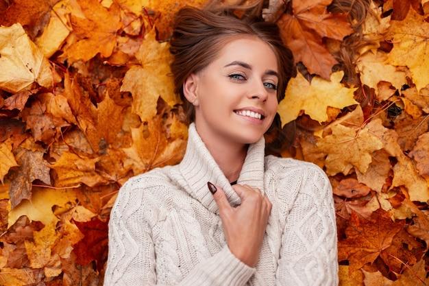 Gelukkig mooie jonge vrouw met blauwe ogen met bruin haar in een gebreide modieuze trui rust liggend op de oranje bladeren in het park. aantrekkelijk meisje met een mooie glimlach. uitzicht van boven