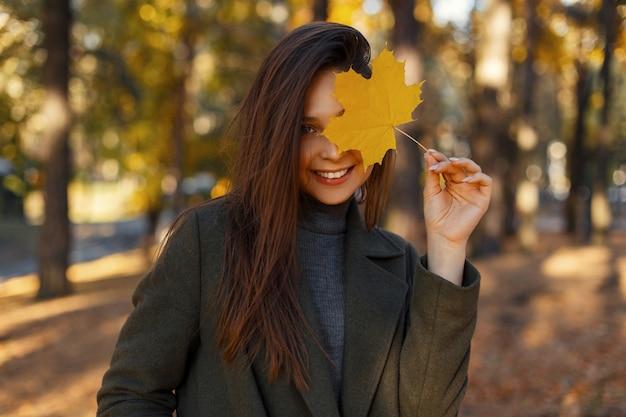 Gelukkig mooie jonge vrouw met een glimlach bedekt haar gezicht met een goudgeel herfstblad en wandelingen in het park
