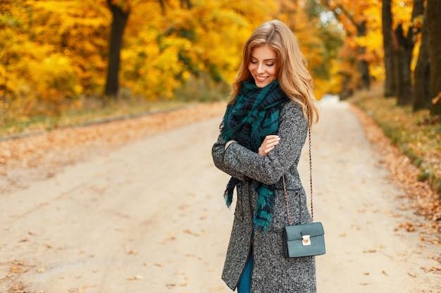 Gelukkig mooie jonge vrouw met een glimlach in stijlvolle kleding met een sjaal poseren in een herfst geel park