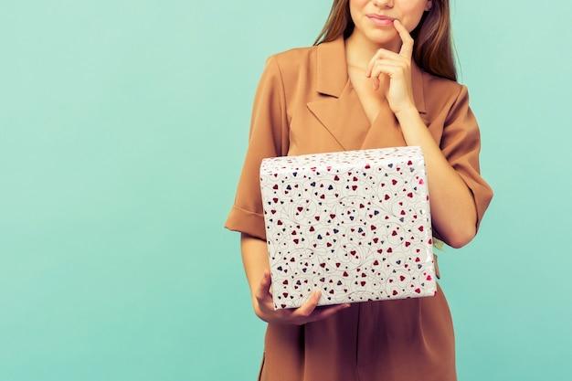 Gelukkig mooie jonge vrouw met geschenkdoos over blauwe achtergrond. kerst- en nieuwjaarsconcept