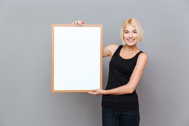 Gelukkig mooie jonge vrouw met leeg wit bord over grijze muur