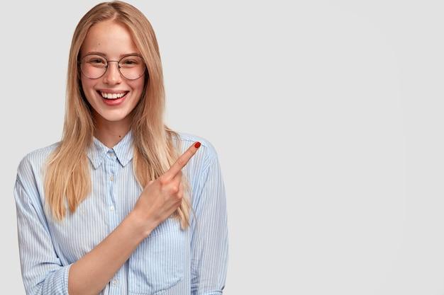 Gelukkig mooie jonge vrouw met zachte glimlach, rode manicure, wijst opzij in de rechterbovenhoek