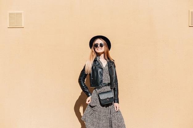 Gelukkig mooie jonge vrouw model in trendy casual look kleding met een hoed en kleine zwarte handtas staat in de buurt van een beige muur op een zonnige dag. vrouwelijke stijl, mode en schoonheid