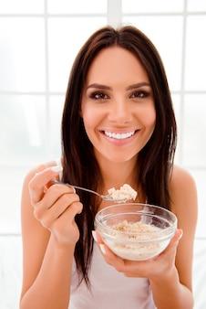 Gelukkig mooie jonge vrouw smakelijke havermout eten en glimlachen