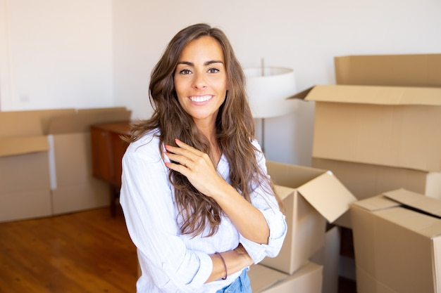 Gelukkig mooie jonge vrouw verhuizen in nieuw appartement, staande voor hoop geopende kartonnen dozen, camera kijken