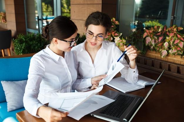 Gelukkig mooie jonge vrouwelijke ondernemers of studenten die op laptop in straat café buiten werken