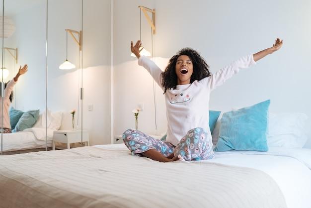 Gelukkig mooie jonge zwarte vrouw ontspannen zittend in het bed