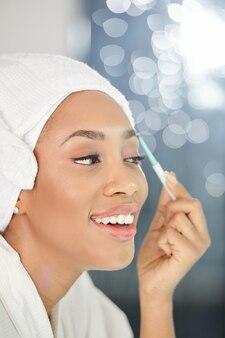 Gelukkig mooie jonge zwarte vrouw wenkbrauwen trimmen met elektrische trimmer voor spiegel na het nemen van een douche in de ochtend