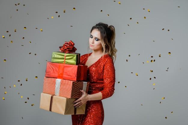 Gelukkig mooie kerst vrouw dragen rode jurk met kerstcadeaus, kerstinkopen, verkoop, vieren