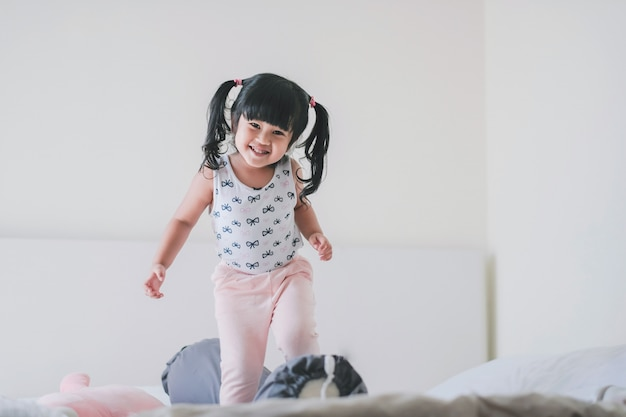 Gelukkig mooie kinderen portret. een drie jaar oud meisje in geluk moment in de slaapkamer
