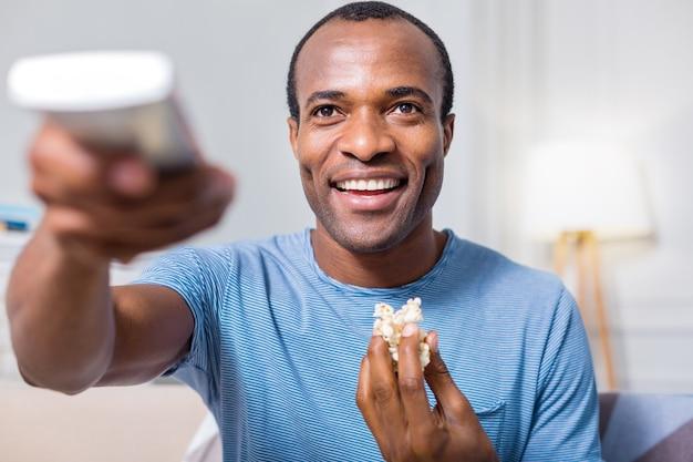 Gelukkig mooie knappe man glimlachend en genieten van popcorn zittend voor de tv