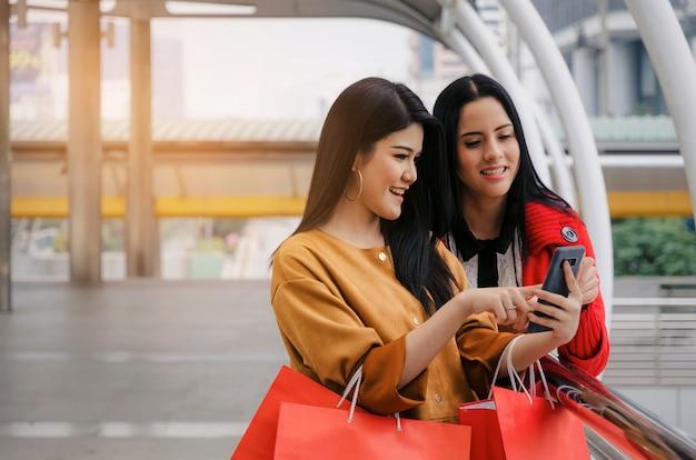 Gelukkig mooie lachende aziatische en blanke jonge vrouw met mobiele telefoon en boodschappentassen te houden