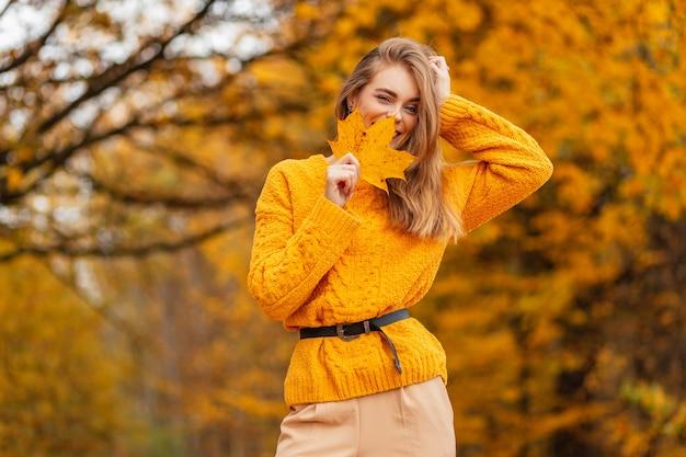Gelukkig mooie lachende vrouw met een positieve stemming in een vintage gebreide trui bedekt haar gezicht met een herfstblad en loopt in een park met gouden herfstbladeren.
