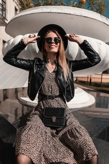 Gelukkig mooie lachende vrouw met zonnebril en mode hoed in zwart leren jas en vintage jurk met modieuze handtas zit in de stad op een zonnige dag
