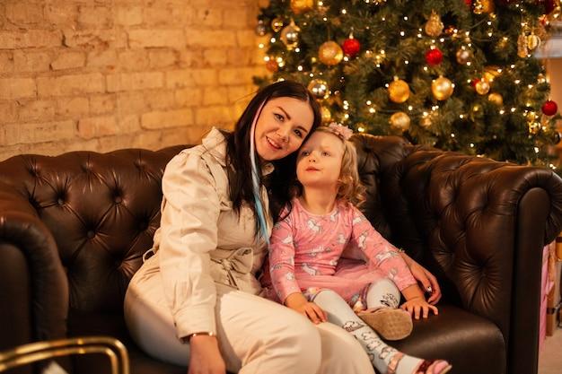 Gelukkig mooie moeder met haar schattige dochtertje meisje in modieuze kleding zit op een leren bank in de buurt van de kerstboom. familie wintervakanties