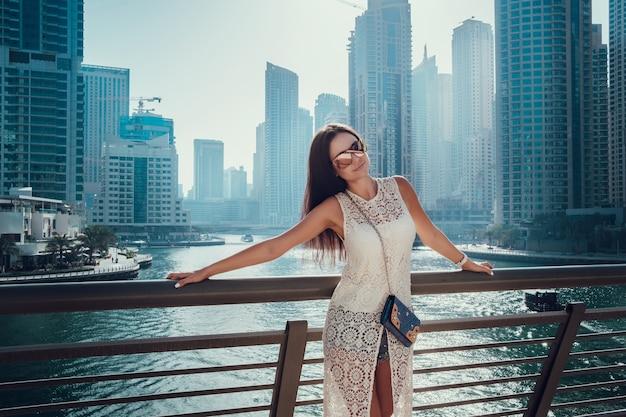 Gelukkig mooie onherkenbaar toeristische vrouw in modieuze witte zomerjurk genieten in dubai