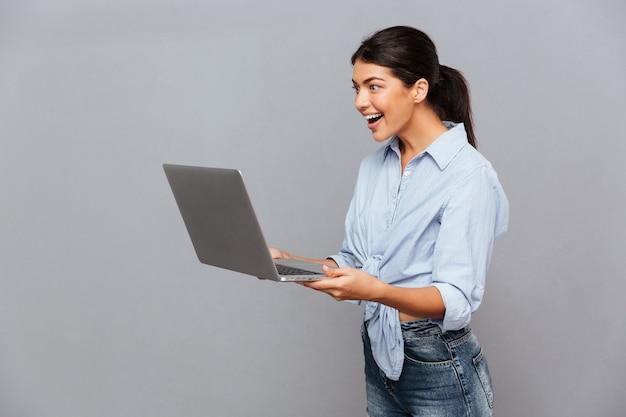 Gelukkig mooie opgewonden vrouw met behulp van laptop geïsoleerd op een grijze muur