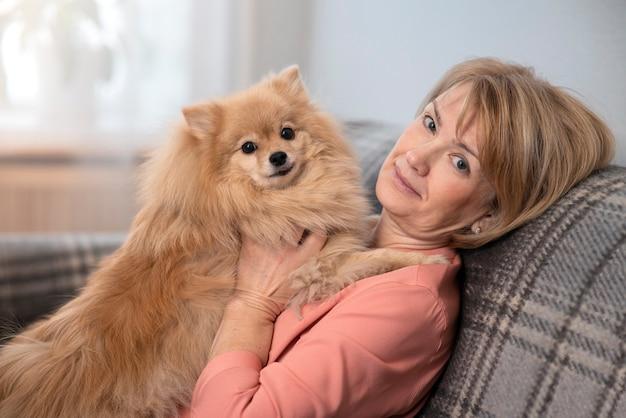 Gelukkig mooie positieve dame, oudere senior vrouw zittend op de bank in de huiskamer met haar