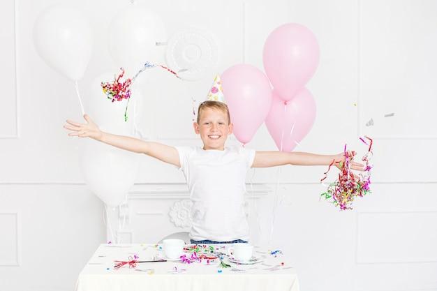 Gelukkig mooie schattige jongen jongen met glimlach op vakantiefeest met ballonnen en confetti in witte kamer