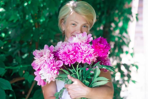 Gelukkig mooie senior vrouw lachend met boeket bloemen
