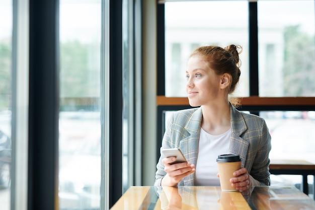 Gelukkig mooie tienermeisje in casual jas zittend aan tafel in café en kijkt uit raam terwijl denken over sms