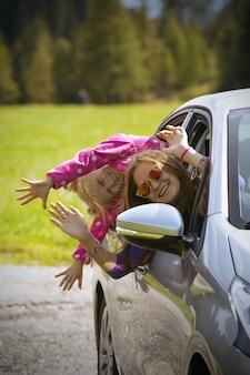 Gelukkig mooie twee lachende zussen meisjes reizen in een auto over de bergen dolomieten, italië. europa