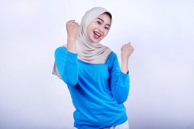 Gelukkig mooie vrouw die hijab en blauw t-shirt draagt, geest glimlach voelt en haar ogen sluit