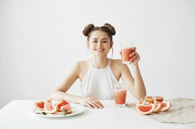 Gelukkig mooie vrouw die lacht zittend aan tafel met glas met gezonde detox verse grapefruit smoothie over witte muur.