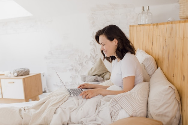 Gelukkig mooie vrouw die op een laptop werkt zittend op een bed in een licht modern huis