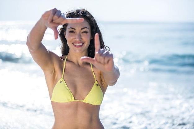 Gelukkig mooie vrouw in bikini vinger frame maken