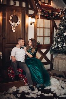 Gelukkig mooie vrouw in jurk kijken naar haar vriendje terwijl het corrigeren van de vlinderdas op zijn shirt met kerstboom