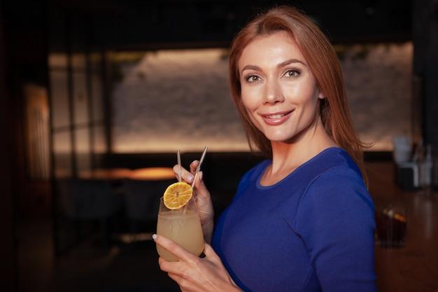 Gelukkig mooie vrouw met cocktail aan de bar, lacht vrolijk naar de camera