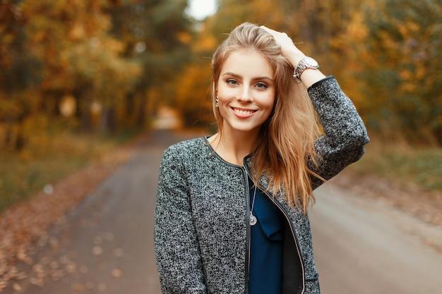 Gelukkig mooie vrouw met een glimlach in een stijlvolle herfstjas poseren in het park
