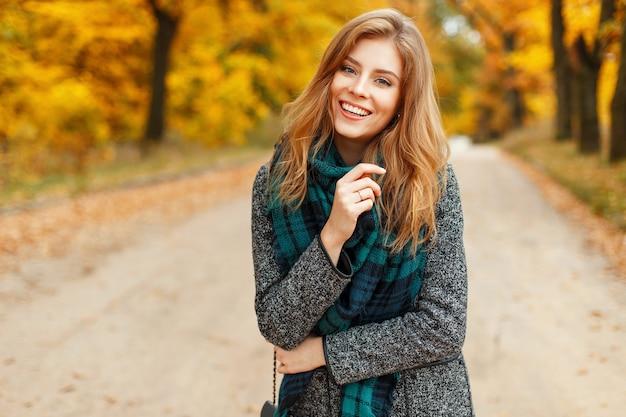 Gelukkig mooie vrouw met een glimlach in een trendy herfstjas met een sjaal op een achtergrond van geel gebladerte
