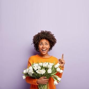 Gelukkig mooie vrouw met knapperig haar, punten hierboven op kopie ruimte, glimlacht teder, houdt witte tulpen, in goed humeur