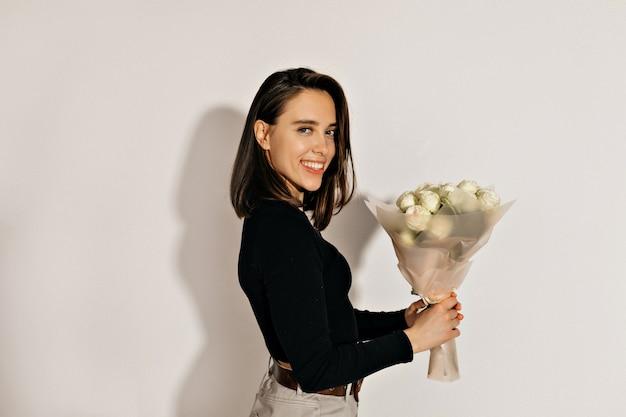 Gelukkig mooie vrouw met kort kapsel poseren op camera en lachend met bloemen