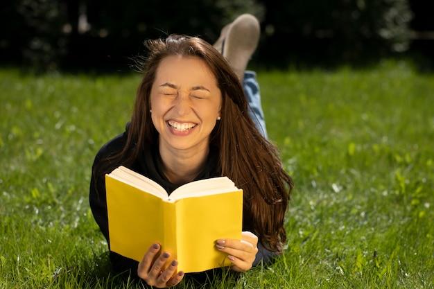 Gelukkig mooie vrouw met plezier in de natuur liggend op groen gras in park met papieren boek in gele kaft