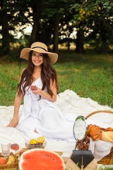 Gelukkig mooie vrouw met rand hoed en witte jurk terwijl staande te houden mand met brood in zomer park