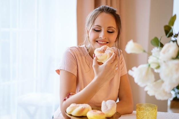 Gelukkig mooie vrouw zitten aan de tafel en met een taart