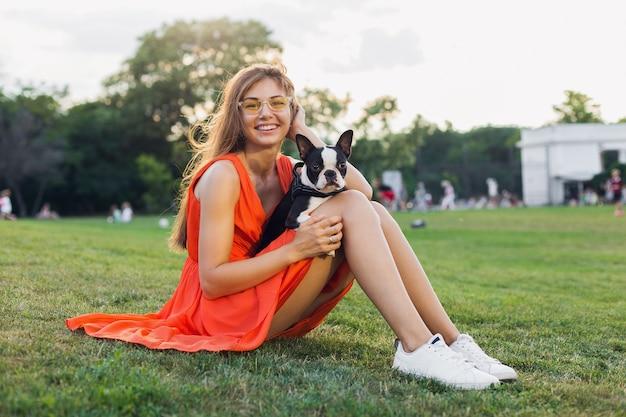 Gelukkig mooie vrouw zittend op het gras in zomer park, boston terriër hond houden, glimlachend positieve stemming, oranje jurk, trendy stijl, slanke benen, sneakers, spelen met huisdier, ontspannen