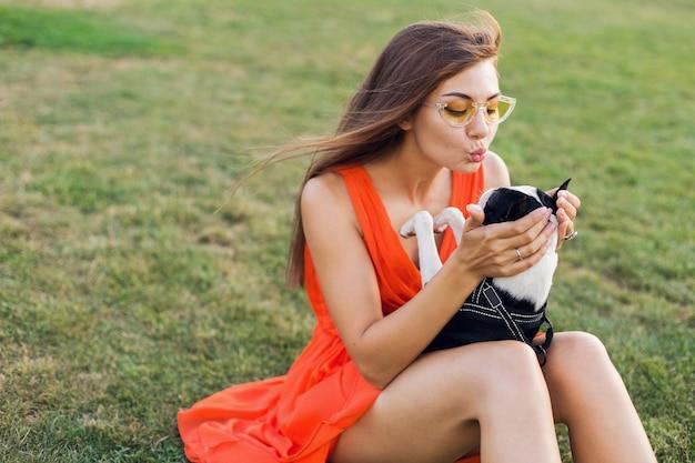 Gelukkig mooie vrouw zittend op het gras in zomer park, houden van boston terriër hond, kussen, oranje jurk, trendy stijl dragen, spelen met huisdier