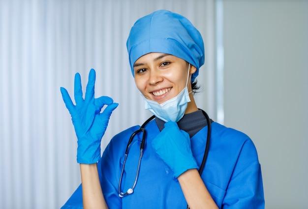 Gelukkig mooie vrouwelijke vrijheidsdokter in blauw ziekenhuispak met stethoscoop glimlachend en ok-teken tonen wanneer gebruikt chirurgisch gezichtsmasker opstijgen, kijken naar camera terwijl pandemie eindigt.