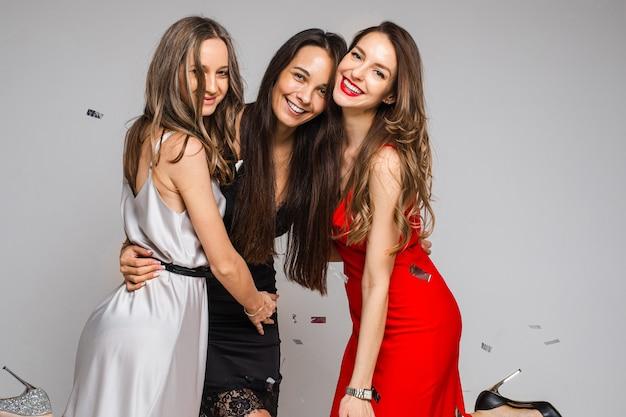 Gelukkig mooie vrouwen knuffelen tijdens het samen vieren, geïsoleerd op een grijze muur