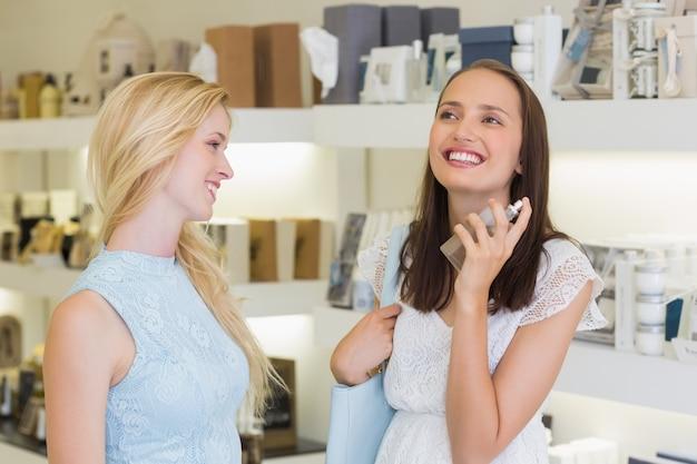 Gelukkig mooie vrouwen spuiten parfum
