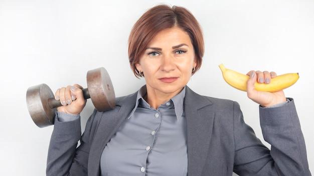 Gelukkig mooie zakenvrouw in een pak tilt een halter en een banaan in haar handen