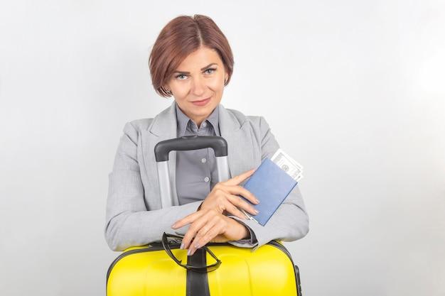 Gelukkig mooie zakenvrouw met paspoort en bagage op reis gaan. vakantie en vermaak. zoek naar plaatsen om te reizen.